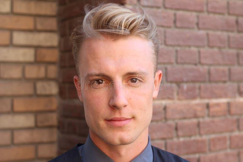 Concept anglais de beauté de monsieur Portrait du jeune et bel homme posant au-dessus du fond marron Fin vers le haut image libre de droits