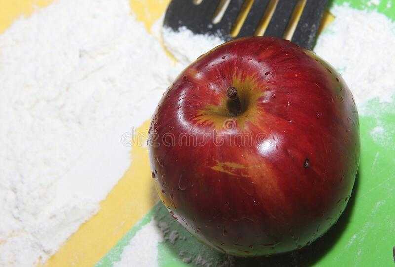 The concept of an Apple as an ingredient for making a filling for baking. The fruit of red color lies on the color boards studded. With white wheat flour royalty free stock images