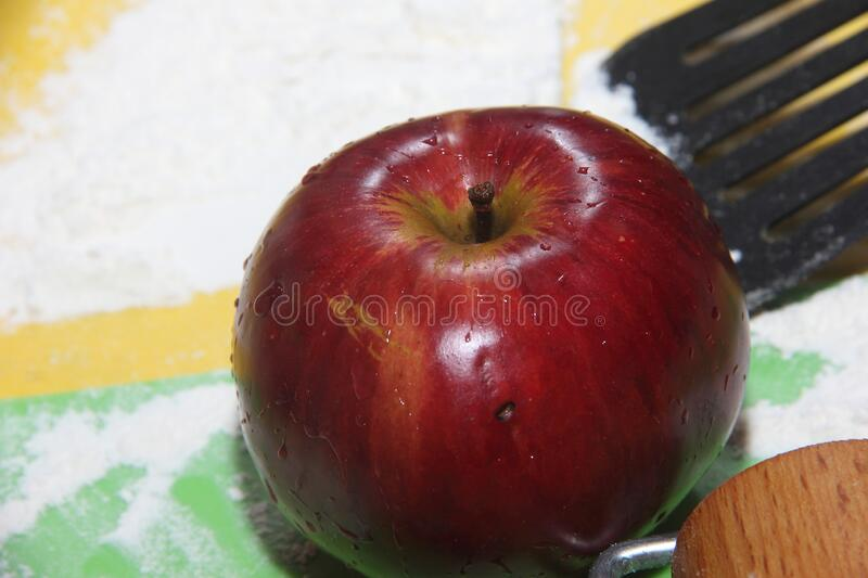 The concept of an Apple as an ingredient for making a filling for baking. The fruit of red color lies on the color boards studded. With white wheat flour stock photo