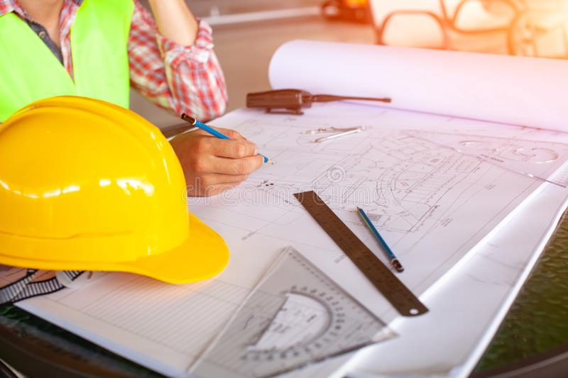 Concept architects,engineer holding pen pointing equipment architects On the desk with a blueprint in the office, Vintage, Sunset royalty free stock photography