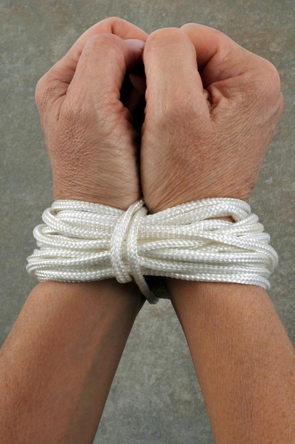 Hands tied up with a rope stock photography