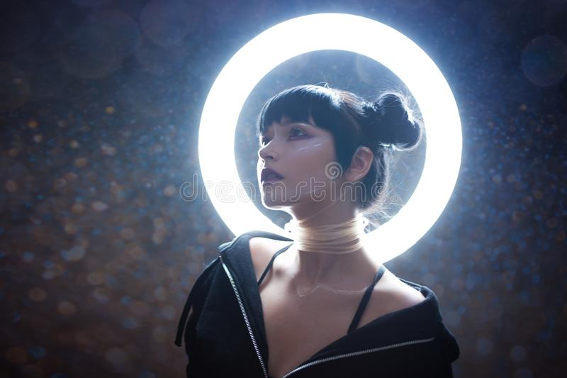 Concept of artificial life. Beautiful young woman, futuristic style. Portrait against a glowing circle royalty free stock photography