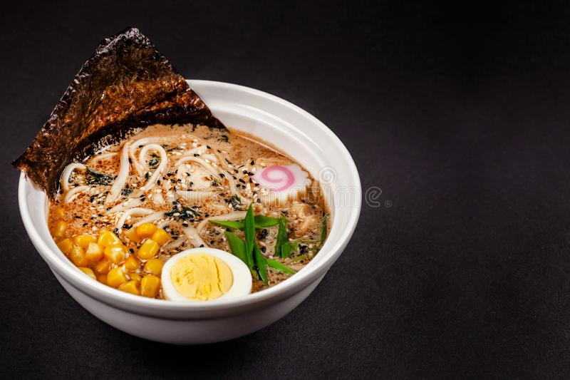 Concept of Asian cuisine. Ramen soup with Chinese noodles, egg, corn, green onions and fish seasoning. Japanese or Chinese dish. On black background royalty free stock photos