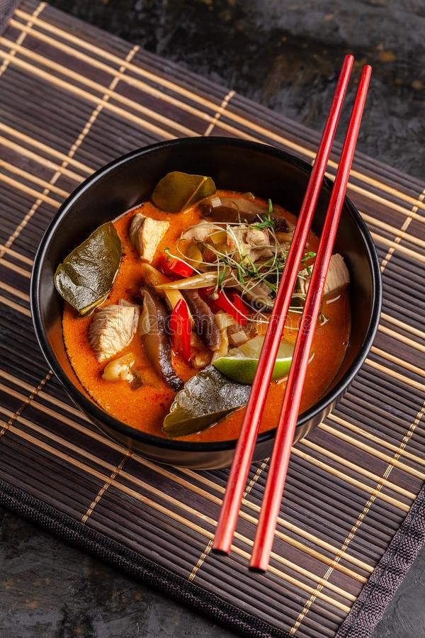 Concept of Asian cuisine. Thai soup Tom yam of chicken broth and coconut milk, mushrooms, chicken, chilli peppers, and vegetables. Japanese dish in black. Top stock photos