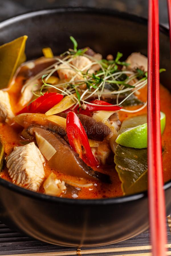 Concept of Asian cuisine. Thai soup Tom yam of chicken broth and coconut milk, mushrooms, chicken, chilli peppers, and vegetables. Japanese dish in black. Top royalty free stock images
