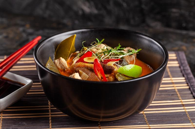 Concept of Asian cuisine. Thai soup Tom yam of chicken broth and coconut milk, mushrooms, chicken, chilli peppers, and vegetables. Japanese dish in black. Top royalty free stock photos