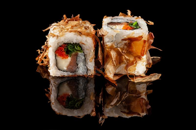Concept of Asian cuisine. Two rolls of sushi with different fillings on a black background with the age for Japanese menu. Concept of Asian cuisine. Two rolls of stock photography
