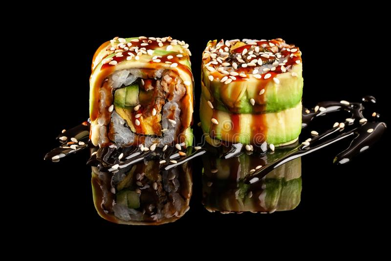 Concept of Asian cuisine. Two rolls of sushi with different fillings on a black background with the age for a Japanese menu. For a cafe, restaurant, sushi bar royalty free stock photos