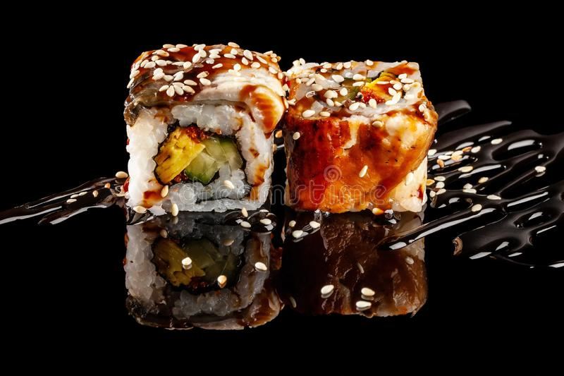 Concept of Asian cuisine. Two rolls of sushi with different fillings on a black background with the age for a Japanese menu. For a cafe, restaurant, sushi bar stock photo