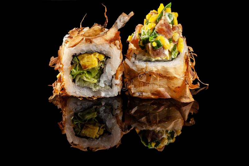 Concept of Asian cuisine. Two rolls of sushi with different fillings on a black background with the age for a Japanese menu. For a cafe, restaurant, sushi bar royalty free stock photo