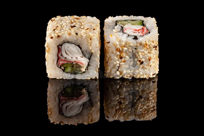 Concept of Asian cuisine. Two rolls of sushi with different fillings on a black background with the age for a Japanese menu. For a cafe, restaurant, sushi bar stock photography