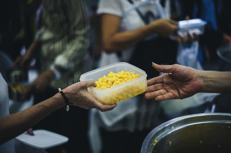 The concept of asking for food with hunger: poor people receive food donated by people in society stock photography