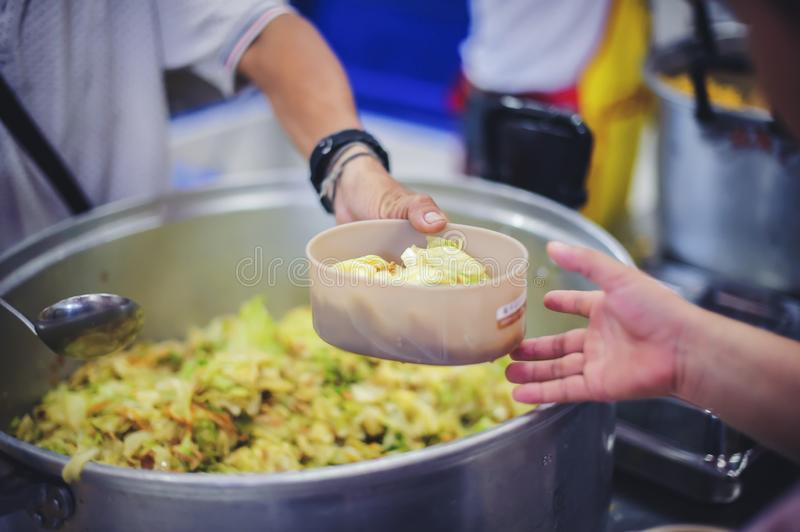 The concept of asking for food with hunger: poor people receive food donated by people in society stock photo