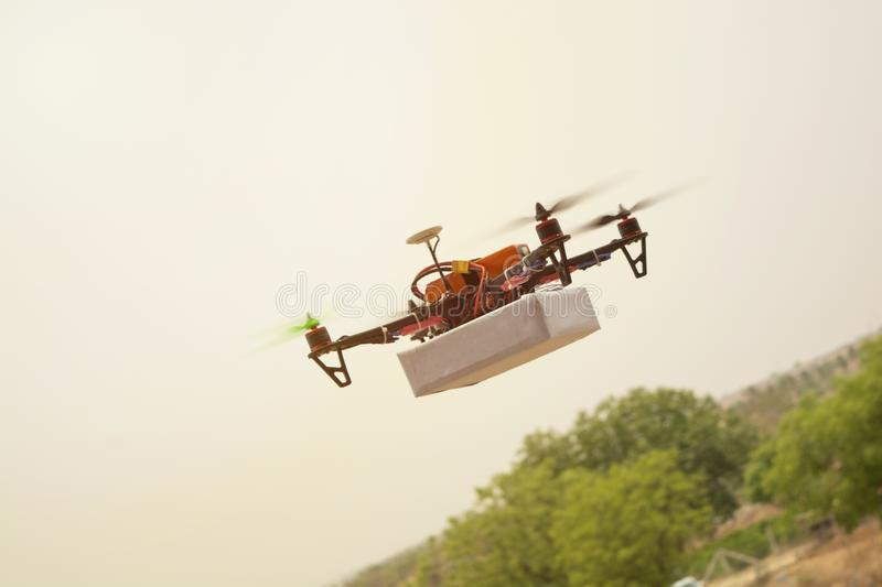 Concept of Assembled Drone quadcopter delivering a package royalty free stock photography