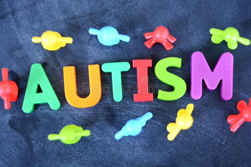 Concept autiste d'enfant avec l'autisme en plastique coloré d'orthographe de lettre sur le fond foncé photographie stock libre de droits