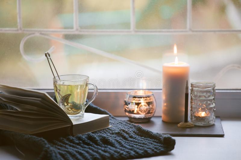 Concept of autumn reading time and romantic, hygge, unplug, mindfulness, Warm, cozy seat opened book, rustic style home decor -. Cup, book, candle, warm plaid stock photography