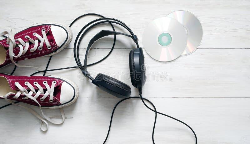 Concept avec des espadrilles de claret, des écouteurs noirs et des Cd étendus images libres de droits