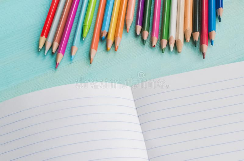 Concept back to school.School accessories, colored pencils, pen with empty notebook on blue wooden background. First of September. drawing. Autumn. Studying at stock photo