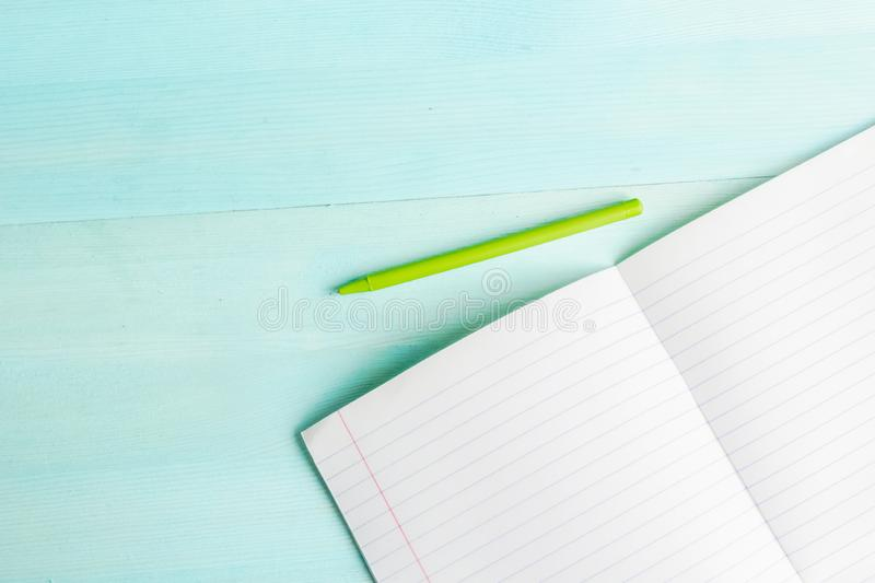 Concept back to school.School accessories, colored pencils, pen with empty notebook on blue wooden background stock photography
