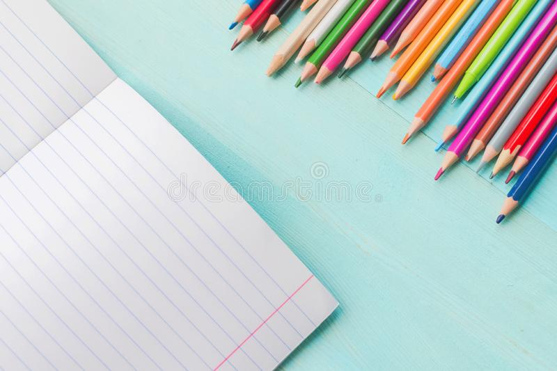 Concept back to school.School accessories, colored pencils, pen with empty notebook on blue wooden background. First of September. drawing. Autumn. Studying at stock photos