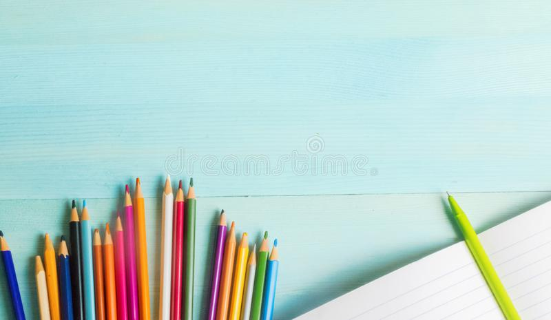 Concept back to school.School accessories, colored pencils, pen with empty notebook on blue wooden background. First of September. drawing. Autumn. Studying at royalty free stock images