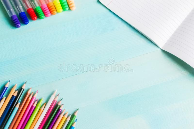 Concept back to school.School accessories, colored pencils, pen with empty notebook on blue wooden background. First of September. drawing. Autumn. Studying at stock images