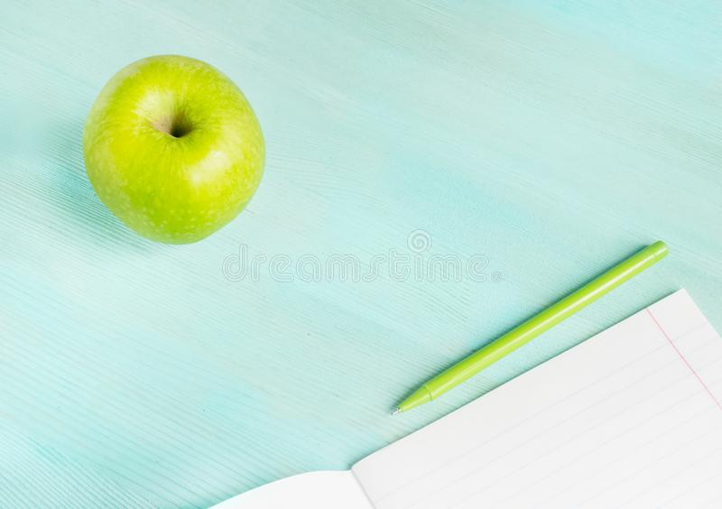 Concept back to school.School accessories, pen with empty notebook on blue wooden background. Concept back to school.School accessories, pen, apple with empty stock image
