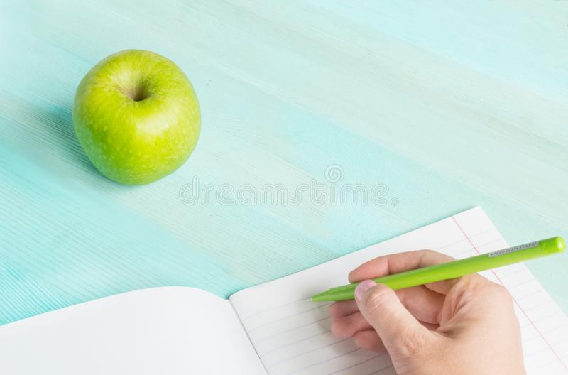 Concept back to school.School accessories, pen with empty notebook on blue wooden background. Concept back to school.School accessories, pen, apple with empty royalty free stock photo