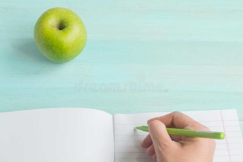 Concept back to school.School accessories, pen with empty notebook on blue wooden background royalty free stock photography
