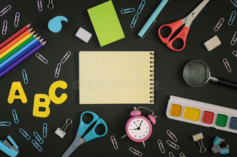 Concept, Back to school. A photo from above, on a black background lie multi-colored school and office supplies. In the stock photography