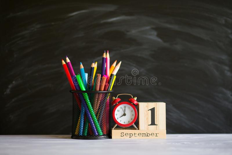Concept back to school. Re alarm clock with color pencils and wooden calendar set on 1st september on blackboard background. stock images