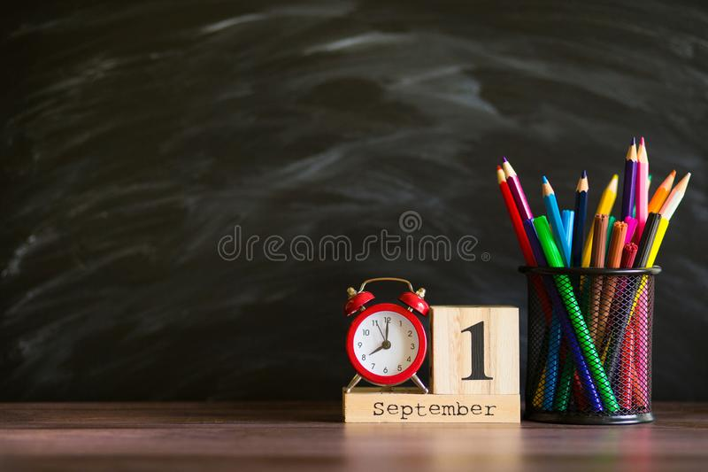 Concept back to school. Re alarm clock with color pencils and wooden calendar set on 1st september royalty free stock photo