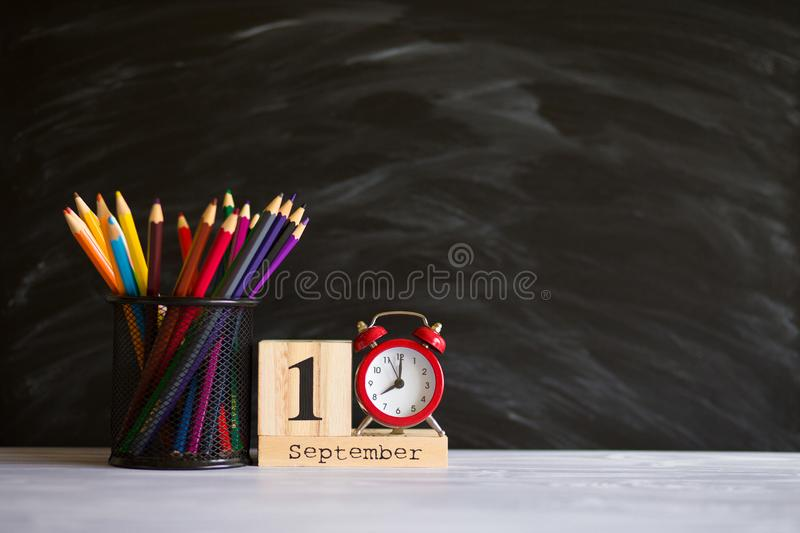 Concept back to school. Red alarm clock with color pencils and wooden calendar set on 1st september on blackboard background. stock photo