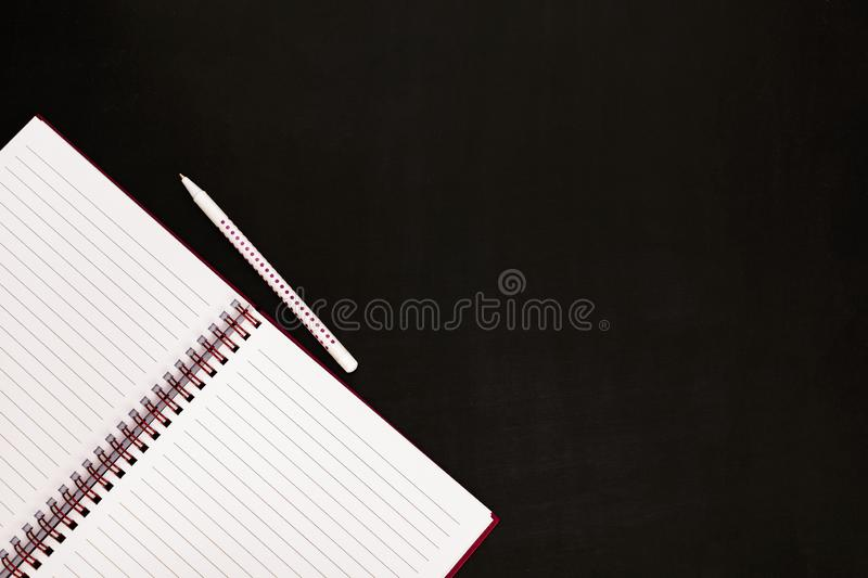 Concept back to school. Stationery - empty open notepad and pen on chalkboard, close up royalty free stock photos