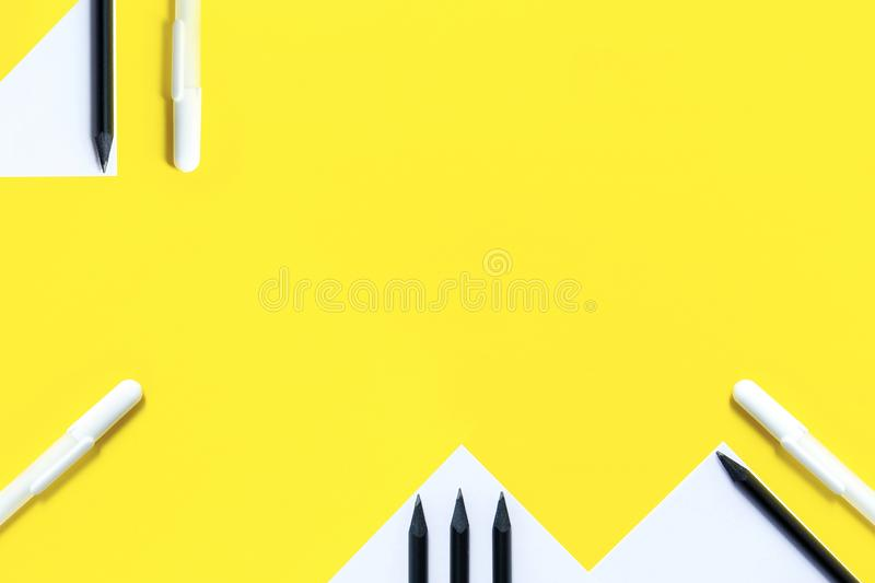 The concept is back to school. White paper, black pencils and white pens are randomly arranged on a yellow background.  royalty free stock image