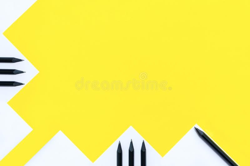 White paper, black pencils and white pens are randomly arranged on a yellow background. The concept is back to school. White paper, black pencils and white pens stock photography