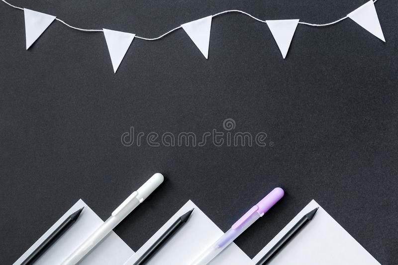 The concept is back to school. White paper, black pencils, white pens and a garland of flags are randomly located on a black backg. Round royalty free stock photo