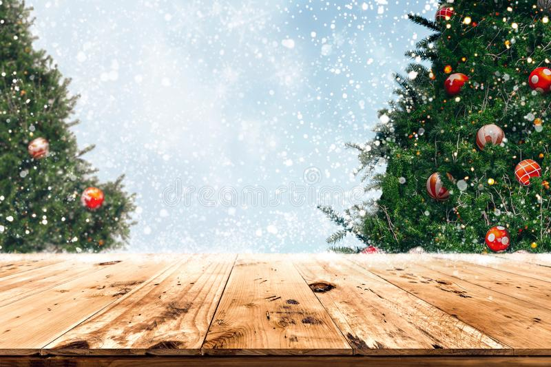 Concept of background in Christmas and New year holidays. Top of empty wood table with beautiful Christmas tree and snowfall  backdrop. ready for your product royalty free stock images