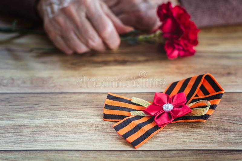Concept background of May 9 Russian holiday Victory Day. St. George`s ribbon on a wooden table, old woman holding in hands a red royalty free stock image