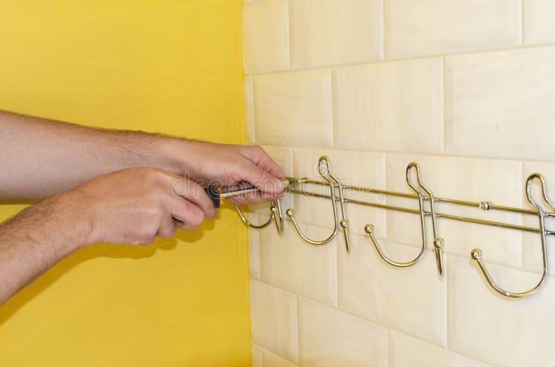 Concept badkamers het remodelleren installatie van hanger, handdoekhouder met een schroevedraaier royalty-vrije stock foto