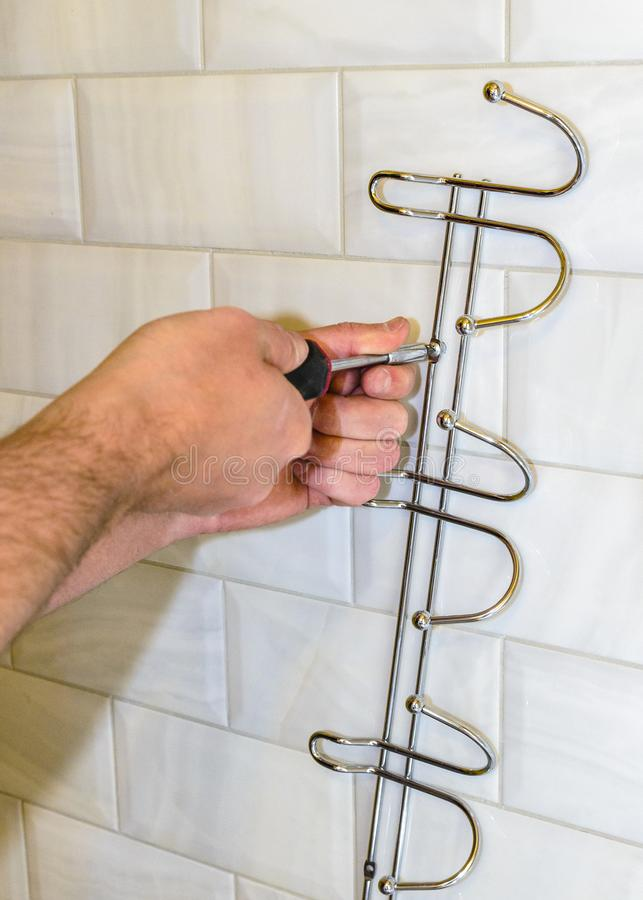 Concept badkamers het remodelleren installatie van hanger, handdoekhouder met een schroevedraaier royalty-vrije stock foto's