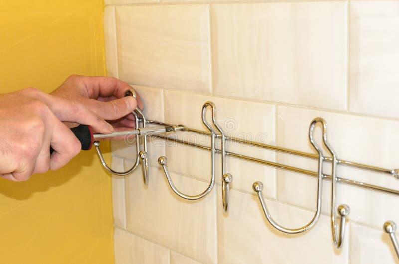 Concept badkamers het remodelleren installatie van hanger, handdoekhouder met een schroevedraaier stock fotografie