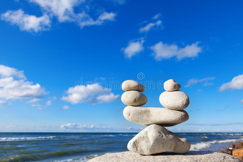 Concept of balance between work and life. Balance stones against the sea. Rock zen in the form of scales.  stock photo