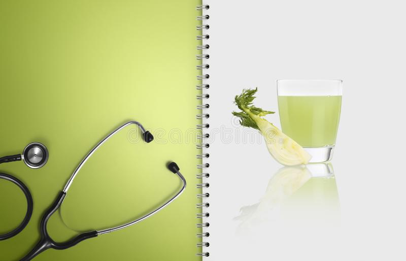 Concept of balanced medical diet with healthy food, paper notebook pages with stethoscope, and fennel juice isolated on white, stock image