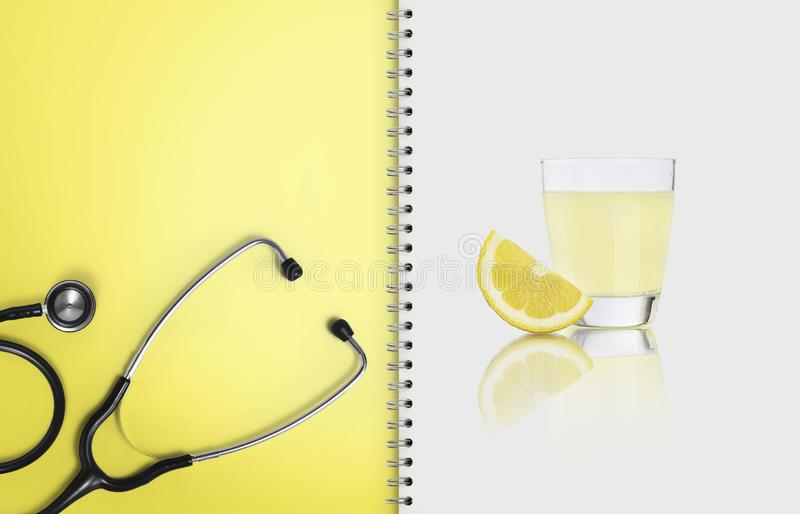 Concept of balanced medical diet with healthy food, paper notebook pages with stethoscope, and lemon fruit juice isolated on white stock images