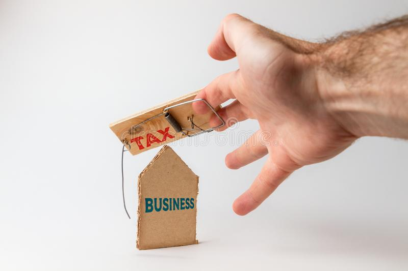 Concept of Bank investments and risks. A man`s hand falls into a mousetrap, with a cardboard insert. Text business and tax royalty free stock images