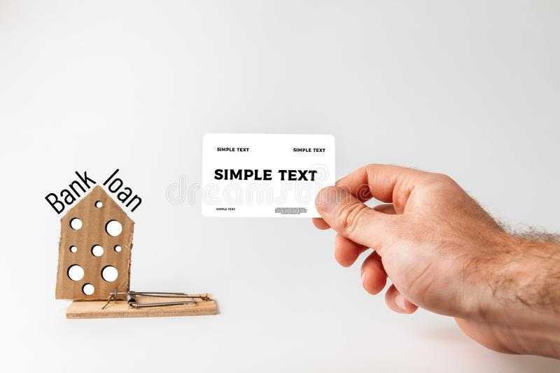 Concept of Bank investments and risks. A man`s hand holds a Bank card, and next to it is a mousetrap with a cardboard house with stock images