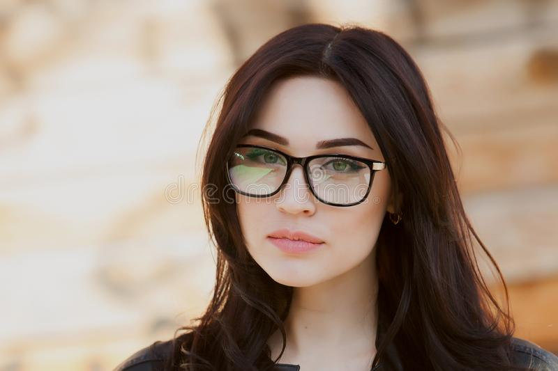 Concept: beautiful eyes, beautiful smile, vision, perfect skin Portrait of a beautiful girl with glasses, eyes closed, shot close- royalty free stock photography
