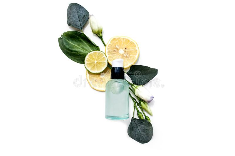 Cosmetic for skin care in a transparent glass bottle on a white background with flower stock photography