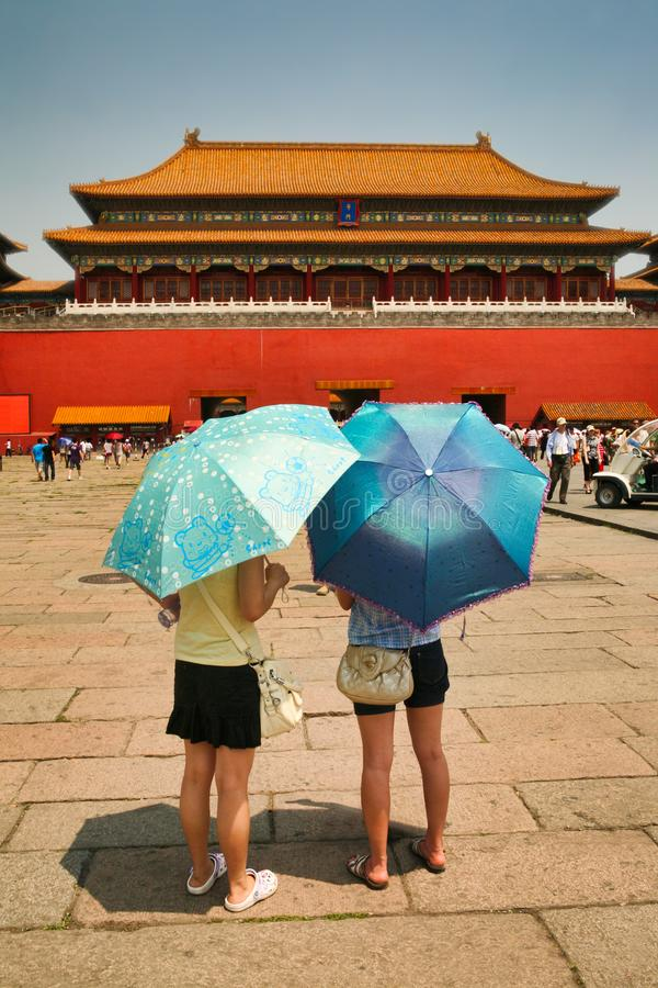 Beijing, China 06/06/2018 Two Chinese girls tourists stand in front of the Meridian Gate - entrance to the Forbidden City under bl royalty free stock images
